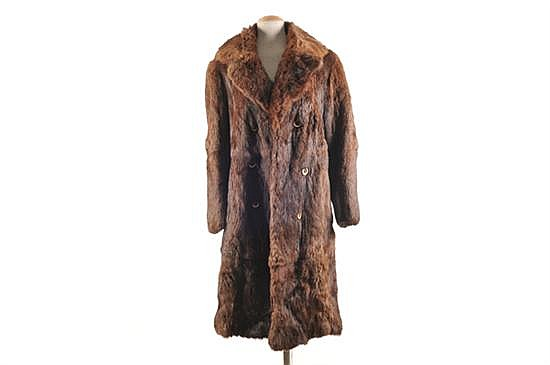 Abrigo largo. Elaborado en piel de petigris, color café. Talla mediana. Presenta rasgaduras y perforaciones en el forro interior.