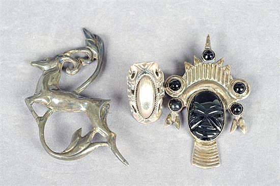 Dos prendedores y un anillo. Medida 9. En plata 0.925. Diseño con onix, a manera de ciervos, máscara y anillo