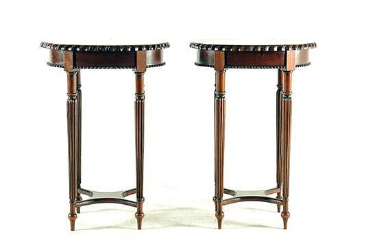 Par de mesas auxiliares. Estilo neoclásico. En madera tallada. Diseño con cubierta oval, chambrana en