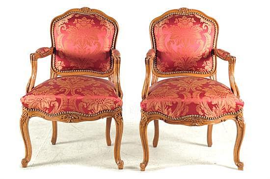 Par de sillones. Estilo francés. En madera tallada. Diseño con respaldos y asientos acojinados; tapicería de damasco en color rojo. 2 p