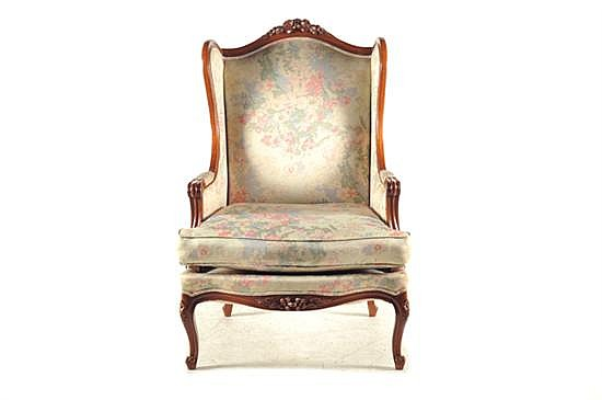 Sillón. Tipo bergere. En madera tallada. Diseño con tapicería floral en color beige y patas tipo cabriolé. Decorado con remate floral.