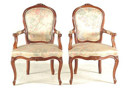Par de sillones. Estilo provenzal. En madera tallada. Diseño con respaldo y asiento acojinado, con tapicería floral beige. Piezas: 2