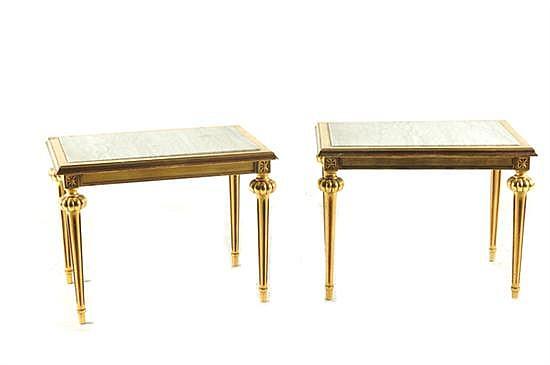 Dos mesas laterales. Estilo Luis XVI. En madera tallada dorada con cubiertas de mármol blanco. Decoración de florones y pilastras. 2 pz