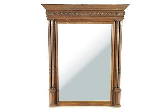 Espejo. Estilo neoclásico. Marco en madera tallada. Diseño rectangular con luna biselada. Con columnas pareadas y basamento tablerado.