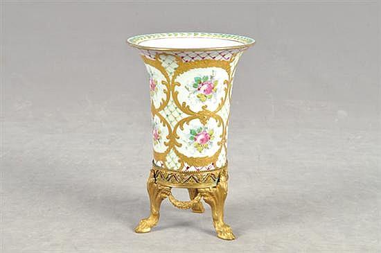 Florero. Elaborado en porcelana Sevres. Diseño con base de metal dorado y fondo blanco. Decoración floral. Dimensiones: 18 cm.