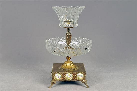 Frutero. En metal dorado con platones de cristal cortado. Diseño a dos niveles, con fuste gallonado. Con motivos vegetales y galantes.