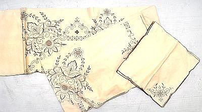 Mantel con doce servilletas. Elaborado en lino. Bordado y deshilado. Diseños florales. Dimensiones: 300 x 170 cm.