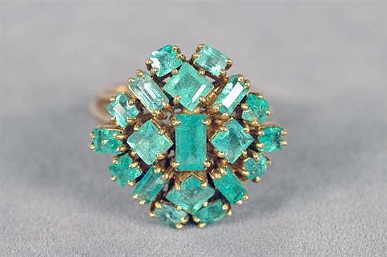 Anillo. Medida 5. En oro de 18k. Diseño con esmeraldas en corte baguete, esmeralda y cuadrillión. Peso: 7.9 grs.