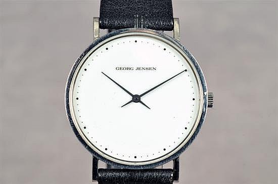Reloj. Origen danés. Marca Georg Jensen. Con caja circular, esfera blanca, índices de punto y manecillas tipo bastón. Pulso de piel.