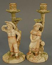 Pair of Royal Worcester figural candlesticks, boy and girl with hats, signed on base Hadley, marked with purple mark. ht. 10 1/4 in.