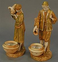 Pair of Royal Worcester figures, each with gilt decoration and carrying vessels emptying into basins, marked with purple marks, ht. ...