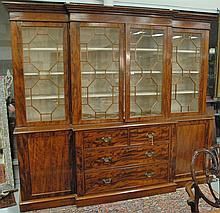 George III mahogany breakfront with large cornice molding over four glazed doors set on base with two over two drawers flanked by tw...