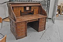 Oak desk having high S roll top, carved sides, and carved and fluted columns, having double bank of bowed drawers with brass handles...