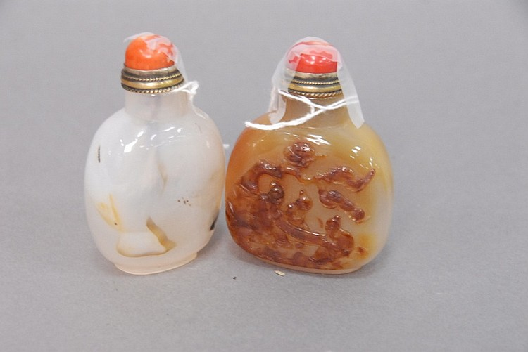 Two agate snuff bottles, one shadow white agate with coral top, and the other agate with carved scene having three scholars under a ...