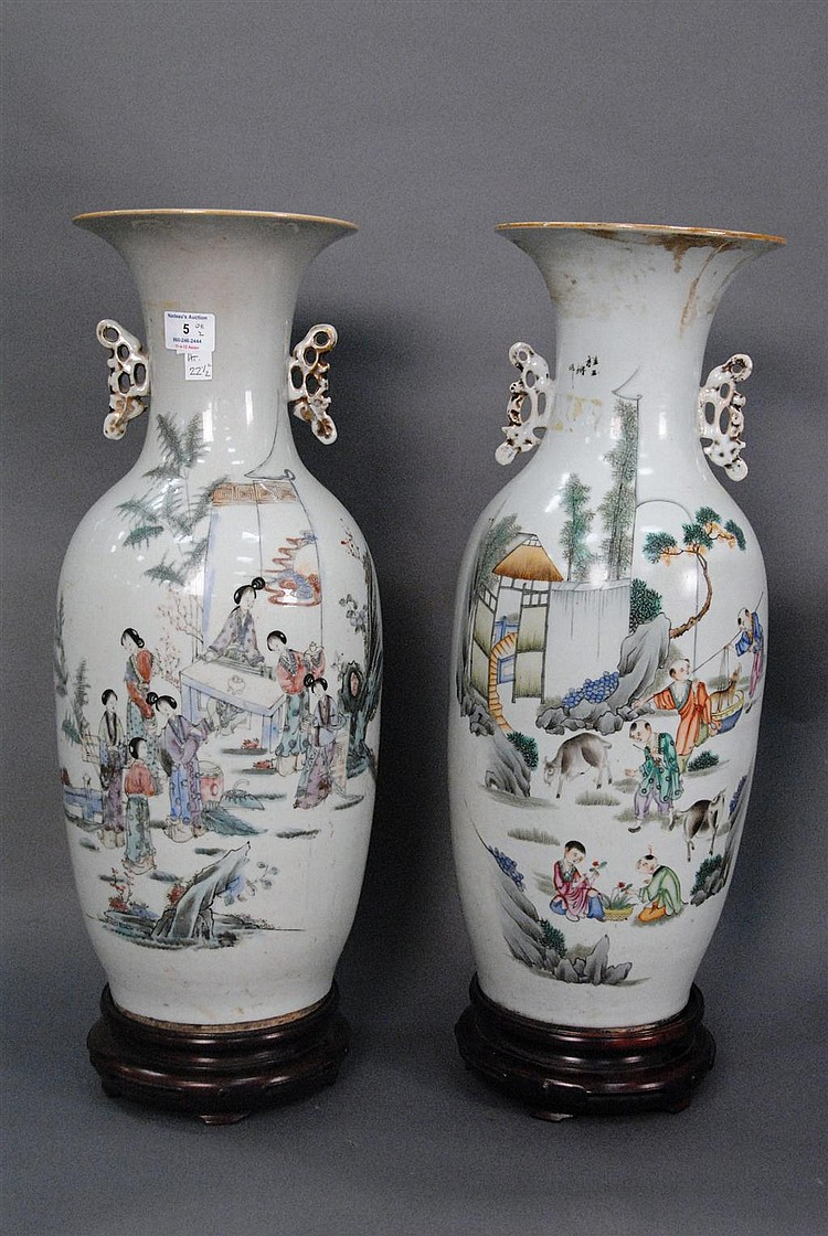 Pair of large Famille rose vases with molded handles on carved wood bases; one with courtyard scene having Guanyin figure and the ot...