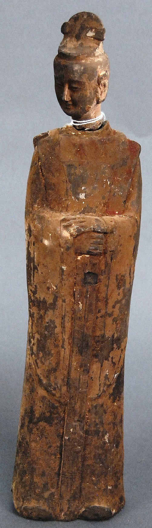 Chinese pottery tomb figure of an official, the standing figure made of grey clay with remnants of red and white colors on a long ro...