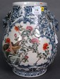 Famille rose vase having an overall blue and white scrolling vine and flower decoration and deer head handles, one panel on each sid...