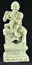 A CHINESE WHITE GLAZED FIGURE OF A LOHAN, seated