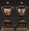Pair of Royal Vienna capped porcelain urns with scenic and figural decoration and heavy gold jeweling on plinth bases, 8