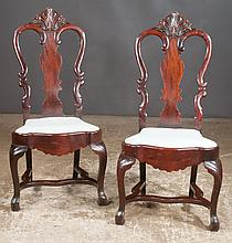 Set of four mahogany side chairs with plume carved urn shape backs, shaped seats, cabriole legs and stretchers, 22