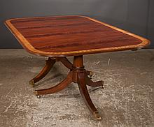 Two pedestal Sheraton style mahogany dining table with satinwood banded top, pedestal has turned columns and three splay legs with brass casters, 48