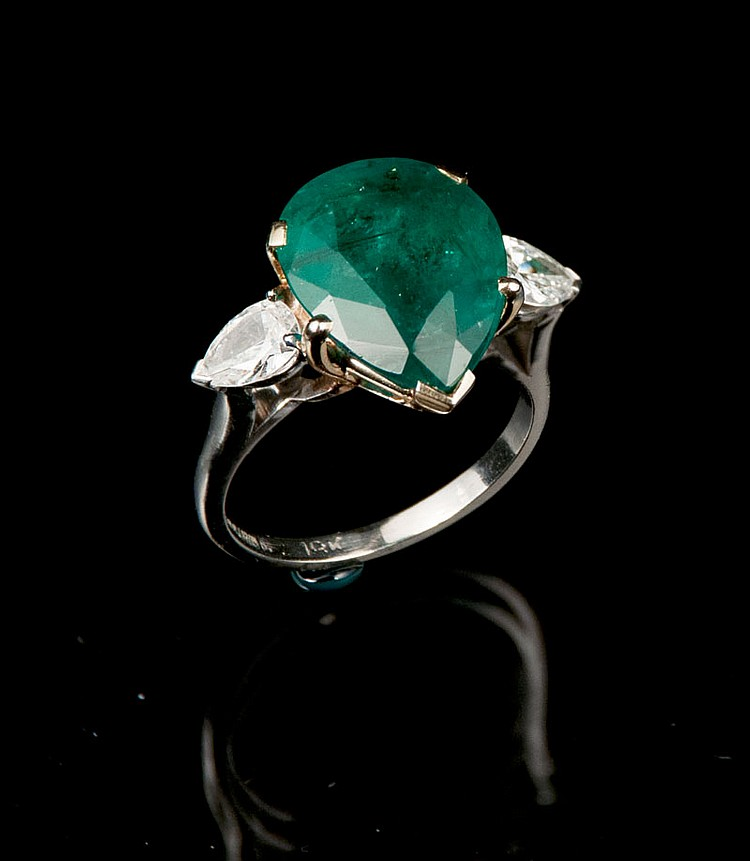 Platinum ring with one pear shaped emerald, approx. 5.50 cts. and two pear shaped diamonds, approx. 0.70 cts.