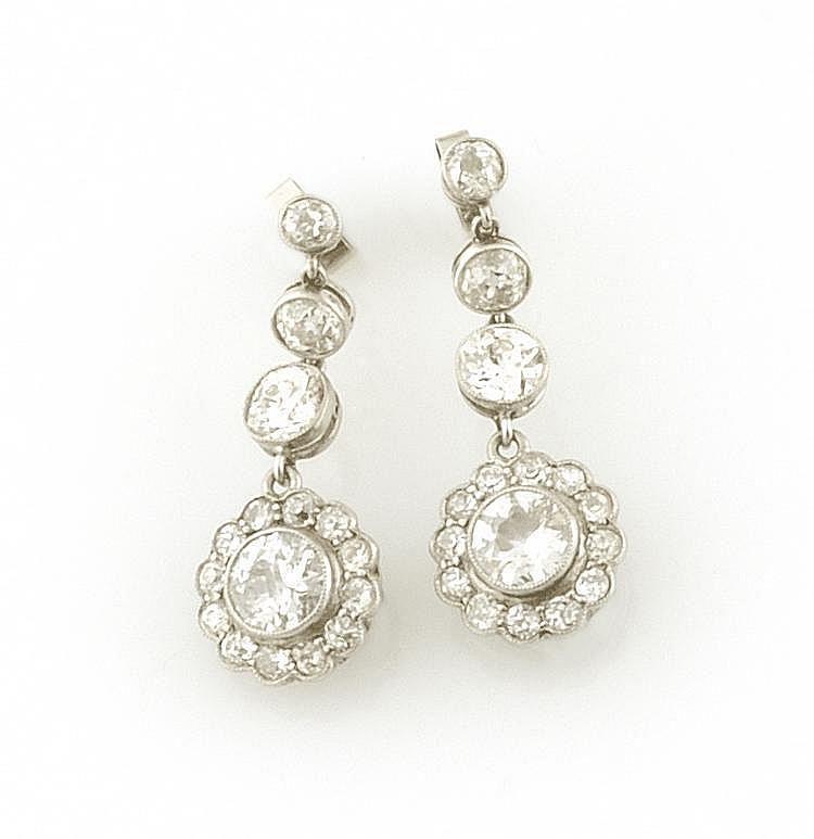PAIRE DE BOUCLES D'OREILLES en or gris ornée d'une chute de diamants de taille ancienne,le dernier dans un entourage de diamants de taille brillant. Poids brut : 5,7 g A DIAMOND AND WHITE GOLD PAIR OF EARRINGS