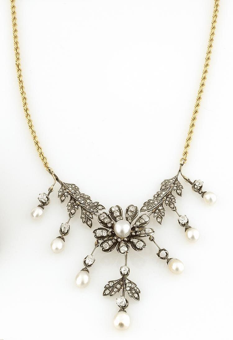 COLLIER en or gris et or jaune, stylisant une fleur dans un entourage feuillagé retenant des pampilles ponctuées de perles fines. La chaine en or jaune. Poids brut : 28,6 g Avec son certificat du LFG attestant sept perles fines. A NATURAL PEARL,