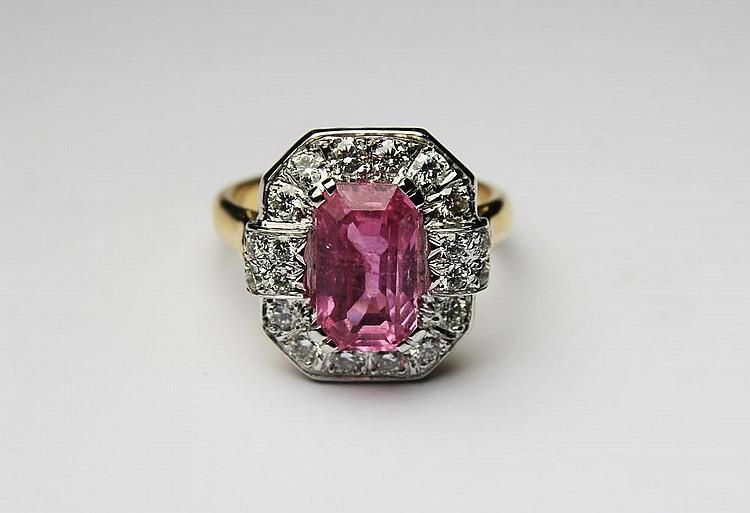 BAGUE en or gris et or jaune ornée d'un saphir rose de taille émeraude d'environ 2,50 carats dans un entourage de diamants de taille brillant. Poids brut : 7,8 g TDD : 54