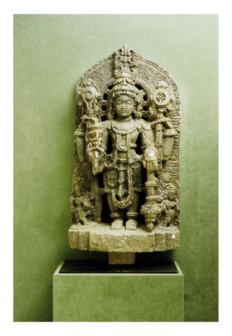 Inde du sud. 11ème siècle.   Importante stèle en grès sculpté de Vishnu debout entouré  de parvati et laksmi.   H. 100 cm.