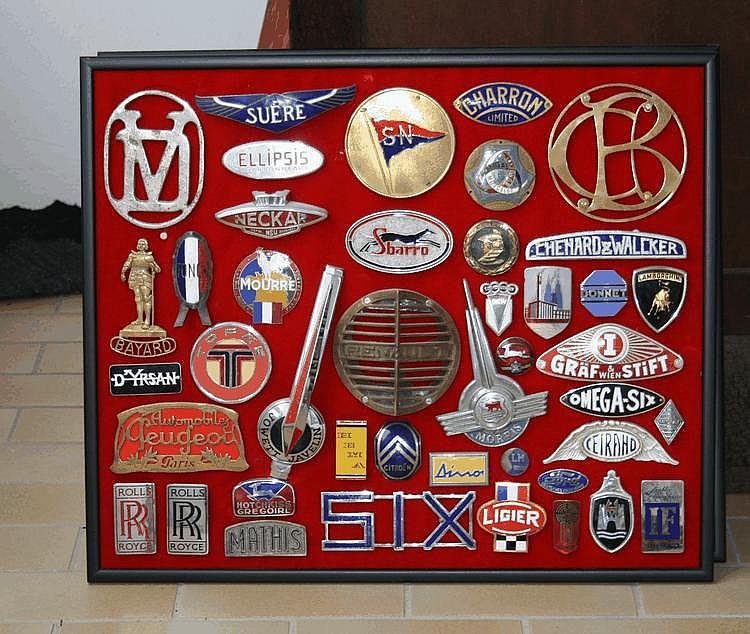 Œuvre originale de Lucien Loreille représentant un assortiment de badges émaillés et monogrammes de diverses marques automobiles, 62 x 52 cm, plus de 50 éléments dont Iso, Bizzarini, Talbot, Buchet Ariès, Benz, etc...