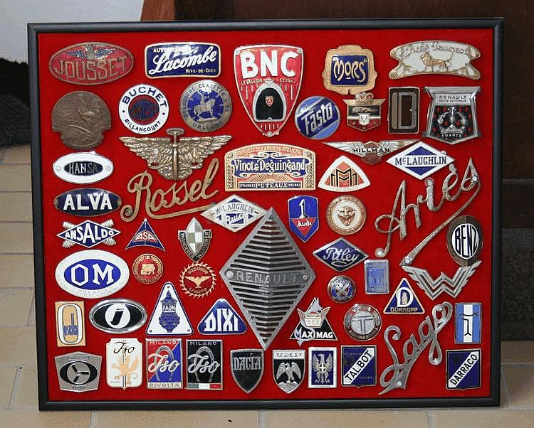 Œuvre originale de Lucien Loreille représentant un assortiment de badges émaillés et monogrammes de diverses marques automobiles, 62 x 52 cm, plus de 40 éléments dont Rolls Royce, Motobloc, Suère, Ligier, Lamborghini, etc...