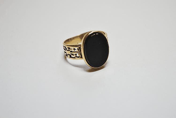 BAGUE en or jaune ornée d'une onyx de taille ovale, la monure ciselé et ajourée.  Poids brut : 7,1 g TDD : 61