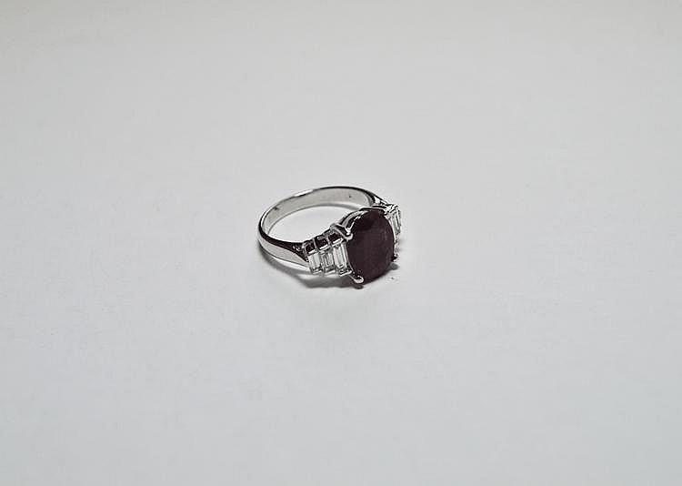 BAGUE en or gris ornée d'un rubis de 2,55 carats probablement Birman de taille ovale dans un entourage de trois diamants de taille baguette.  Poids brut : 5,5 g TDD : 53.  Avec son certificat AIGS