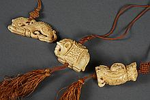 THREE CARVED PENDANTS - Likely ivory; on a silk cord; in the form of an elephant, an owl and a dragon. Varnished. Unsigned. Conditio...