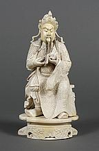 CHINESE CARVED IVORY FIGURE OF GUAN GONG - Unusual scholarly figure of the warrior Guan Gong reading a book and seated on an elevate...