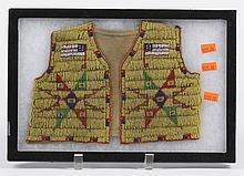 LAKOTA (SIOUX) CHILD'S BEADED HIDE VEST - Fully beaded front; design portrays an American flag, triangles and a central diamond shap..