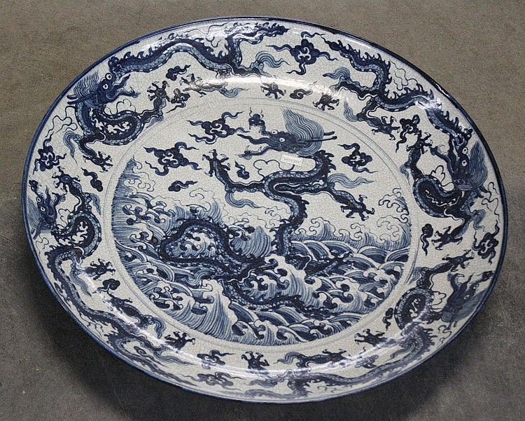 LARGE CHINESE LOW BOWL - Ceramic low bowl with dragon motif; one to center and four around border, blue on crackled pale gray ground...