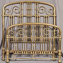 BRASS BED - Antique, of full size, and of tubular construction with curved-top headboard and footboard and metal casters. Condition...