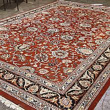 CARPET: HANDWOVEN KASHAN - Wool on a cotton warp with floral, foliate and palmette lattice design on a red field and surrounded by a...