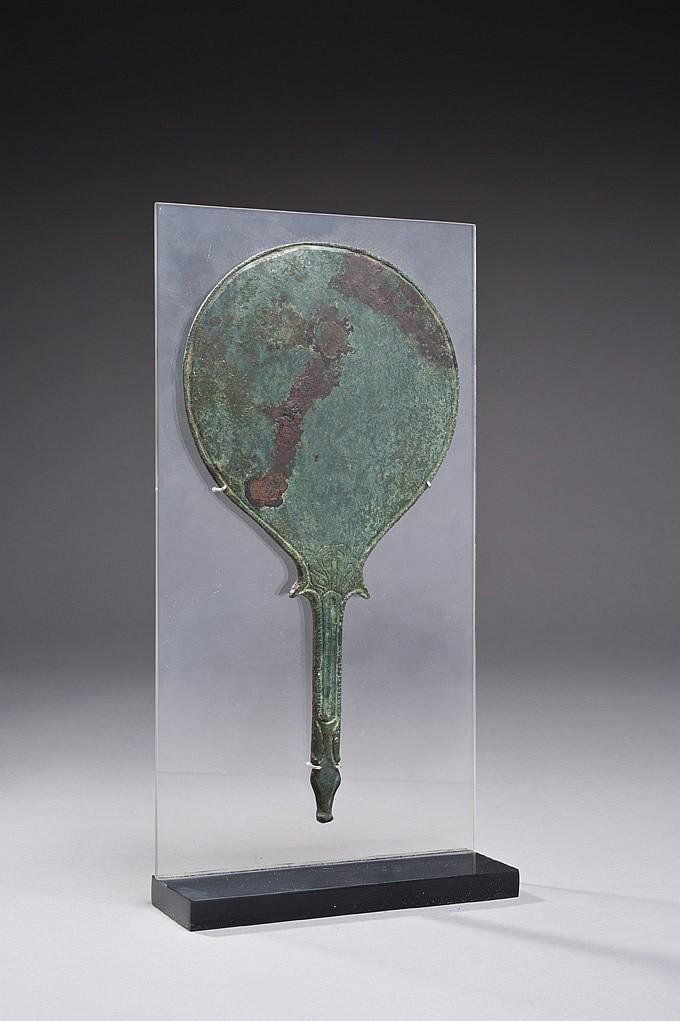 Miroir discoïdal dont le manche est gravé au sommet d'une palmette, et se termine à la base en un protomé animal