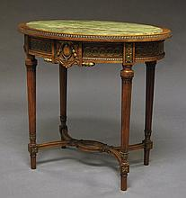 A French carved walnut and onyx topped oval table