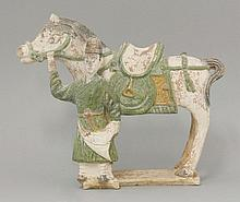 A Tomb Figure, Ming dynasty (1368-1644), of a pony, its reins held by an attendant, details glazed in speckled green and amber, 27.5cm
