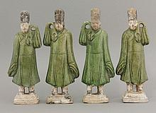 Four earthenware Funerary Models of Sedan Chair Bearers, Ming dynasty (1368-1644), each on stepped plinths, their robes green-glazed and their details black-pencilled,20cm (4)Literature: See 'Catalogue of Late Yuan and Ming Ceramics in the British