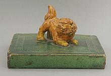 A rare earthenware Carpet Weight,  AFCearly Ming dynasty, the square, green-glazed plinth with a key fret border enclosing an ochre-glazed crouching Buddhist lion, minor chips and wear, dog reset,21.2cm square12cm high