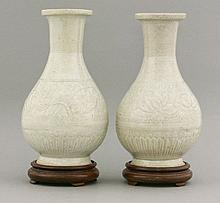 A good pair of Qingbai Vases, Southern Song dynasty (1127-1279), each ovoid body moulded with lotus between zigzag, the base with gadroons, the glaze of one blue-green and the other brown-tinged, 24.5 and 24cm, stands and fitted case