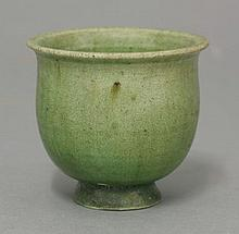 A small earthenware Cup, Tang dynasty (618-906), of flower bud form on short flared foot, the whole under a lime green glaze, pooling crystalline on the interior base, chips to foot restored,4.9cm