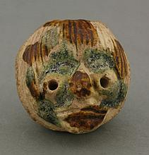 A rare earthenware Head,  AFCprobably Liao dynasty (916-1125), modelled with pierced eyes and incised hair, and of overall walnut form, splashed in sepia and turquoise glazes, 4cm