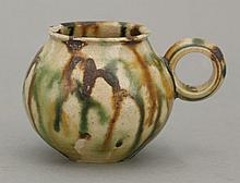 A small Cup, Tang dynasty (618-906), the globular body irregularly splashed in black ochre and green, ribbed ring handle, rim flakes, foot small chip, 4.5cm