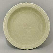 A Ming celadon Bowl, early 15th century, with barbed rim, the centre impressed with a peony within knife carved scrolling foliage, the glaze of even pea-green, 34cm